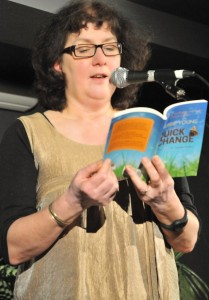 Debbie Young at microphone reading Quick Change