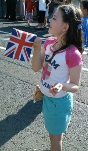 Laura waits patiently for the Olympic torchbearer, Union flag at the ready