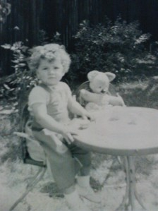 The author, aged about 2, in the garden with her teddy