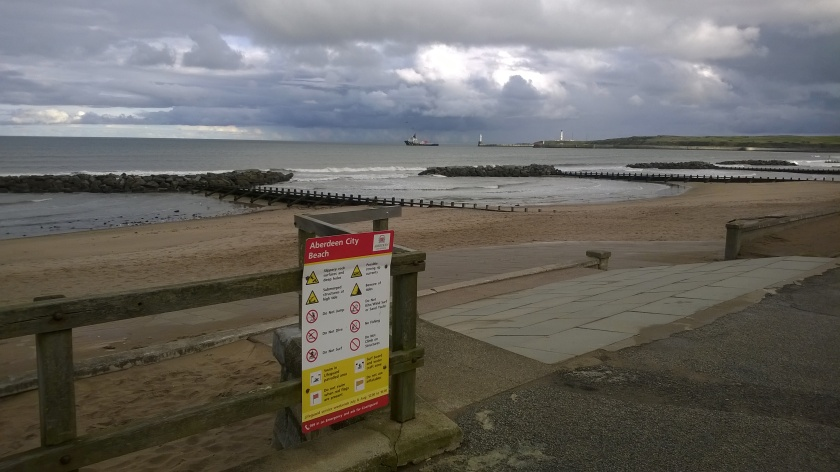 Steely-skied Aberdeen beach with sign listing all the hazards there