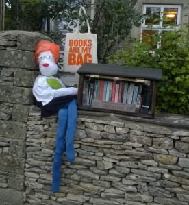 Photo of bluestockinged scarecrow with Books are my Bag bag and Little Free Library