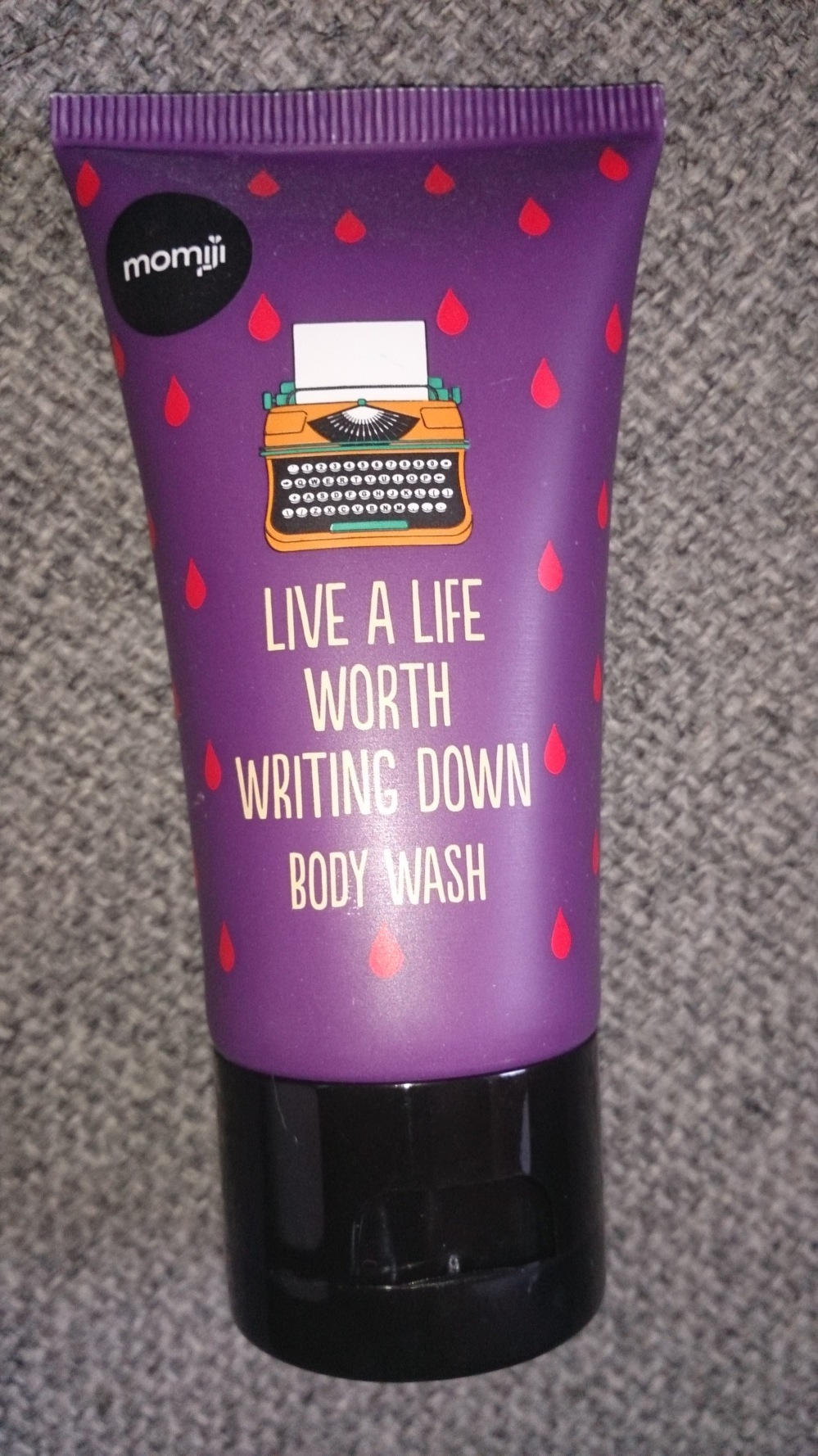 "Body wash tube bearing the caption ""live a life worth writing down"""