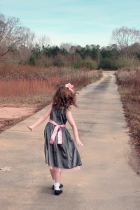 photo of little girl walking down a long path into the distance