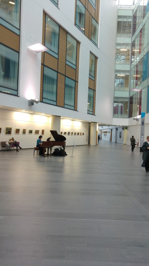grand piano being played in hospital atrium