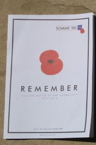 """cover of programme with poppy saying """"Remember"""""""
