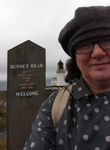 Photo of Debbie in hat and coat at northernmost point of mainland Britain