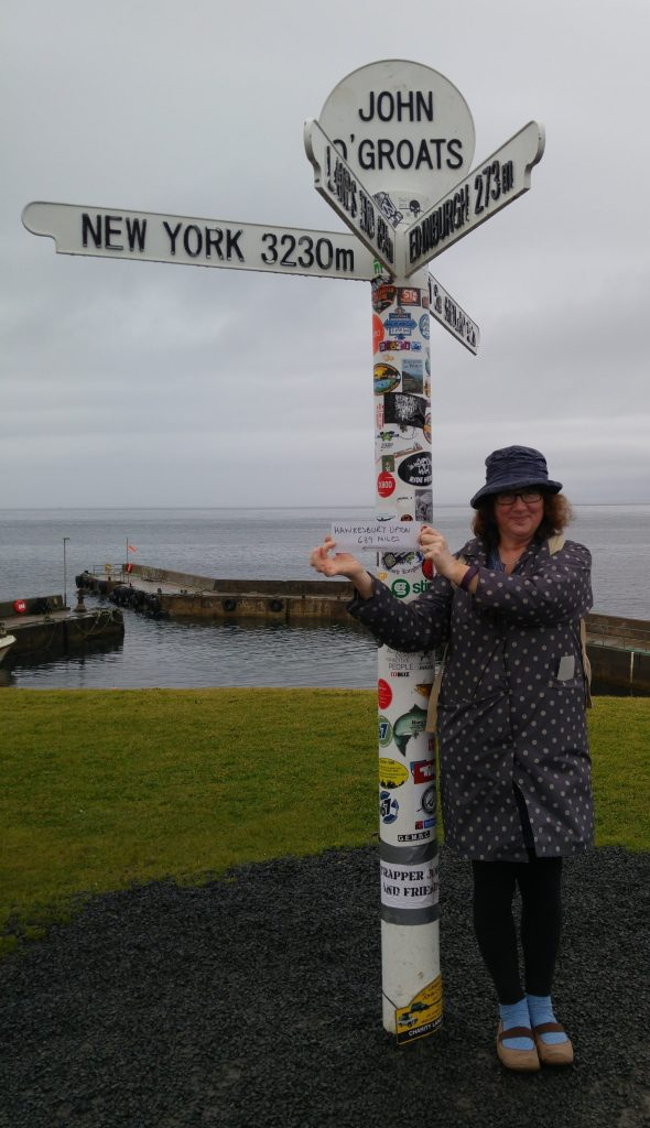 Photo of Debbie holding up sign to Hawkesbury Upton at John O'Groats