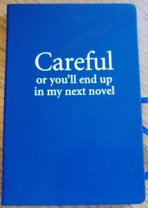 "Cover of notebook with slogan ""Careful or you'll end up in my next novel"""