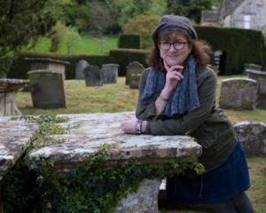 Photo of Debbie smiling in a graveyard