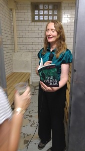 Photo of A A Abbott reading her book in a prison cell