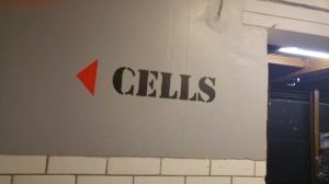 "image of ""Cells"" stencilled in black on to a grey wall"