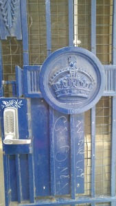 photo of blue gate with government logo and lock