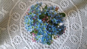 forget-me-not vase photographed from above on lace tablecloth