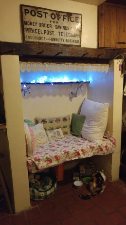 Photo of inglenook bench seat with cushions, fairy lights, etc
