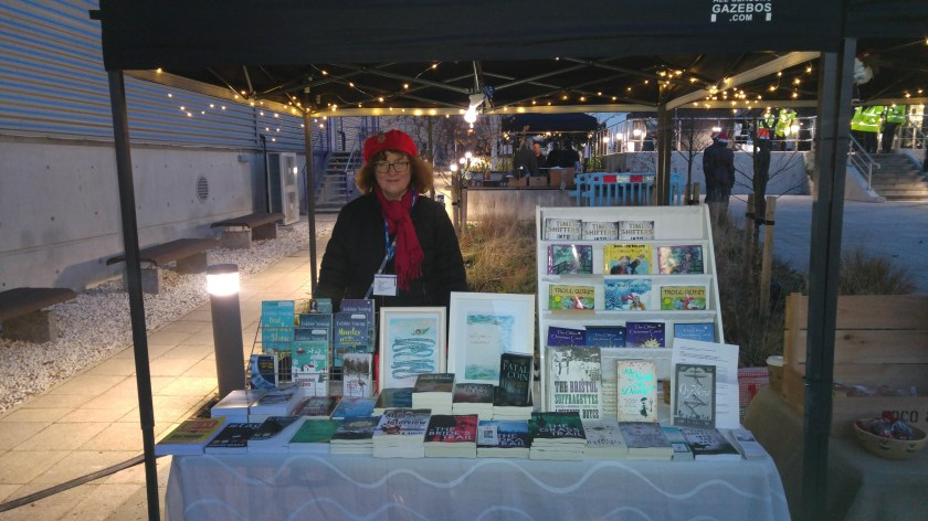 photo of Debbie on stall in darkness beneath fairy lights
