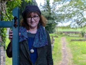 shot of Debbie going through a gate into a graveyard