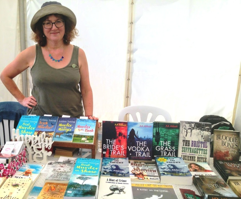 Debbie behind bookstall in khaki hat and vest