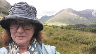 photo of Debbie in rainhat at Glencoe