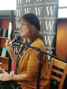 Profile photo of Debbie at microphone with Waterstones banner behind