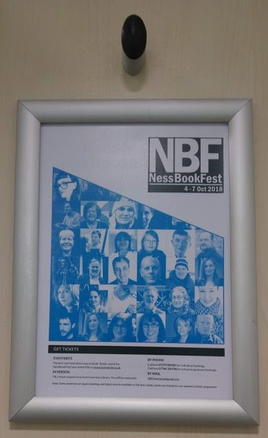festival poster on back of toilet door