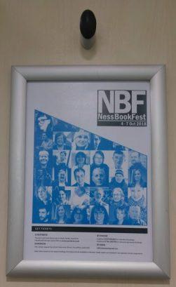 festival poster on back of toilet door