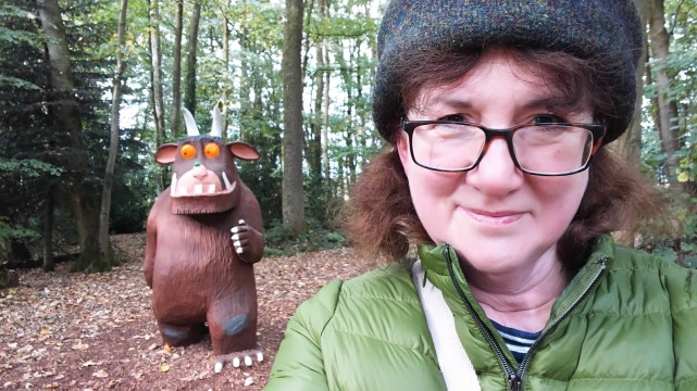 selfie of Debbie with Gruffalo coming up behind her in the woods