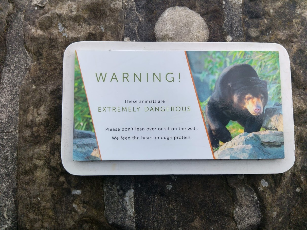 "Sign on bear enclosure at Edinburgh Zoo saying ""Please don't lean over or sit on the wall. We feed the bears enough protein."""