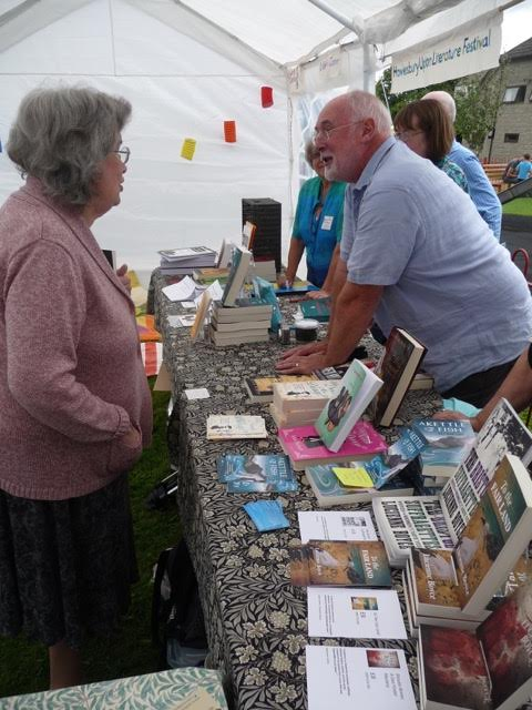 Photo of reader talking to author in show tent