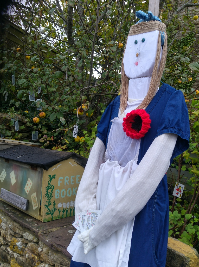 photo of Alice in Wonderland scarecrow wearing a knitted poppy