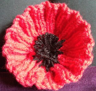 photo of a hand-knitted poppy