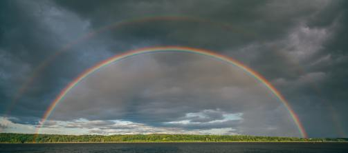image of double rainbow over landscape